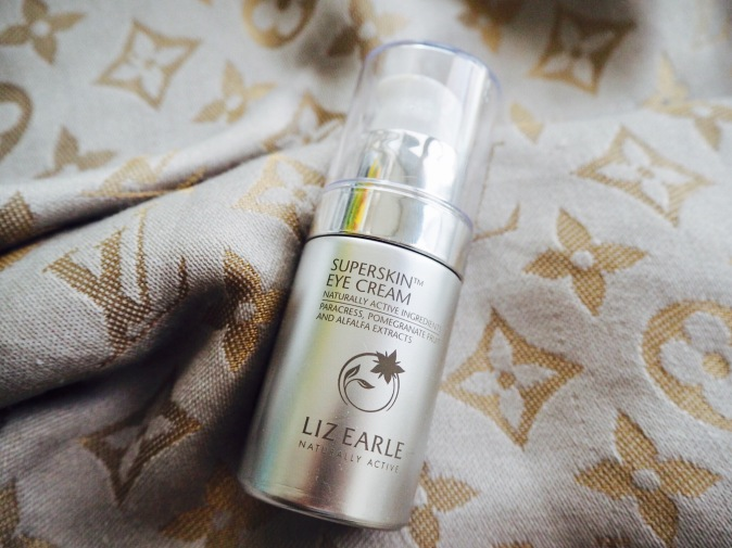 Liz Earle Superskin Eye Cream placed on a Louis Vuitton scarf
