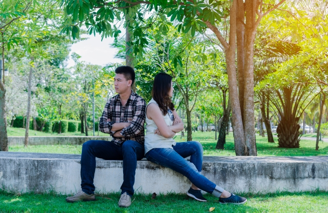 Couple arguing on a bench in a park