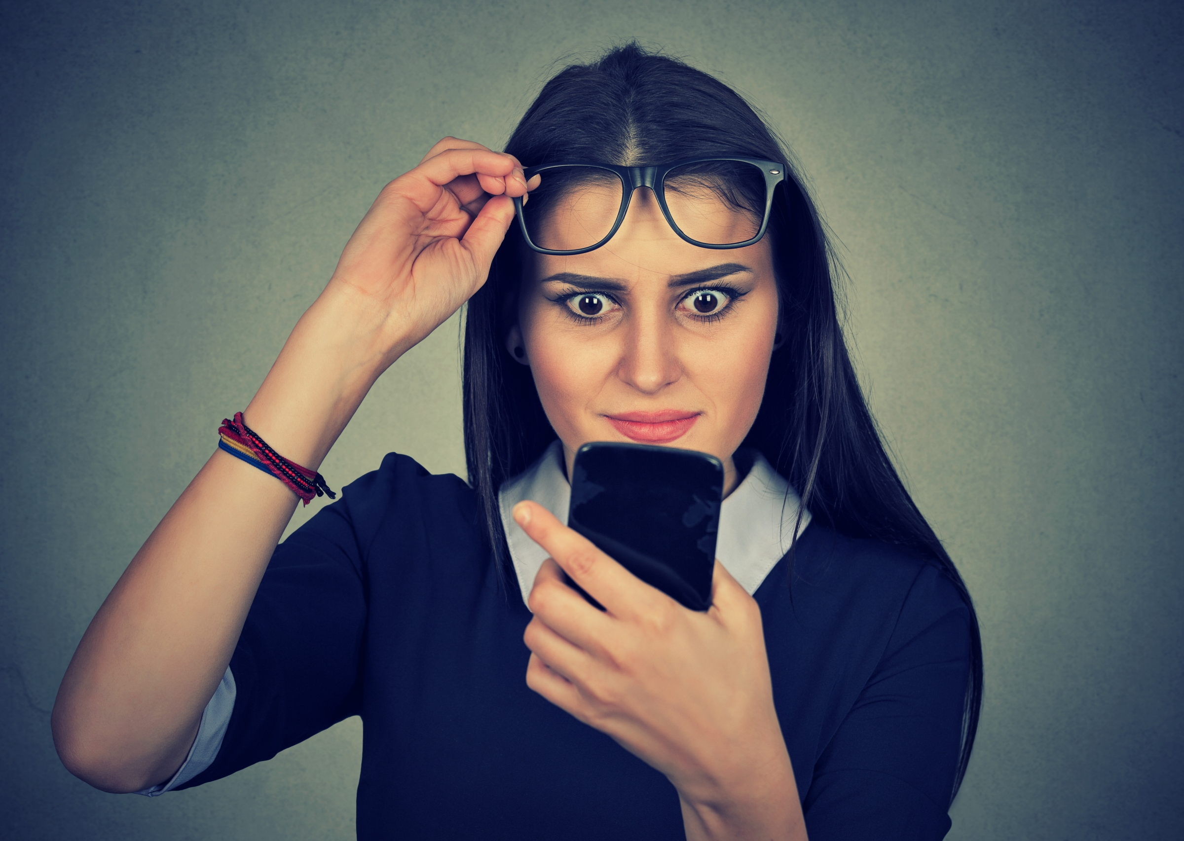 Confused woman looking at mobile