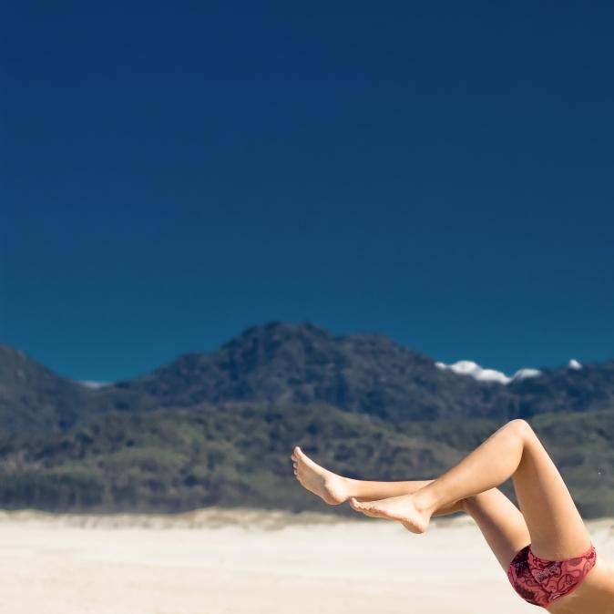 Woman's legs in the air on a beach